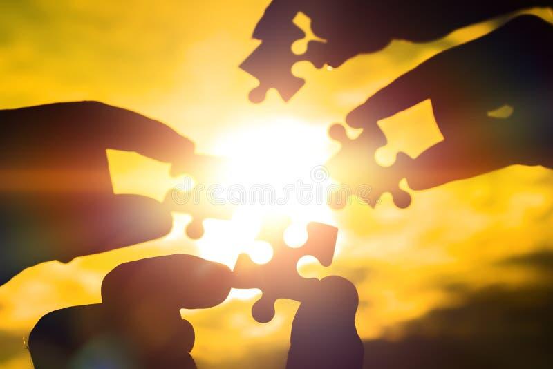 Arbeiten vier Hände zusammen, die versuchen, ein Puzzlespielstück mit einem Sonnenunterganghintergrund anzuschließen Ein Puzzlesp stockbild