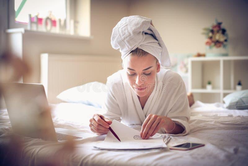Arbeiten vom Bett Junge Geschäftsfrau stockbild