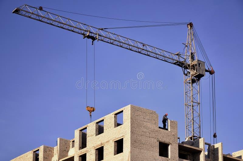 Arbeitende hohe Kräne innerhalb des Platzes für mit die hohen Gebäude im Bau gegen einen klaren blauen Himmel Kran- und Gebäudefu stockfotos