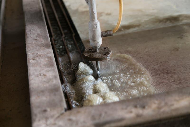 Arbeitende Wasserstrahlmaschine in der Stahl- u. Gelenk Fertigungsindustrie stockfotografie