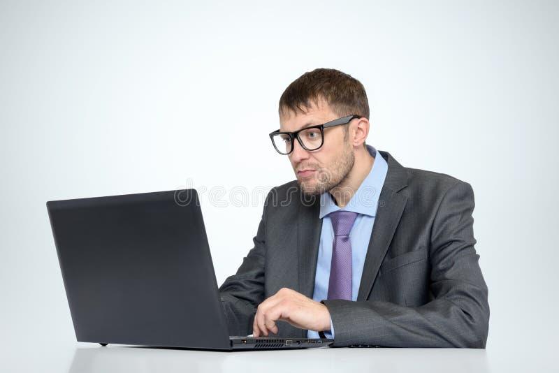 Arbeitender bärtiger Mann in den Gläsern mit einem Laptop auf hellem Hintergrund lizenzfreie stockfotografie