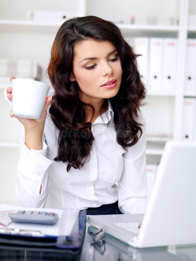 Arbeitender und trinkender Kaffee der jungen Geschäftsfrau stockbilder
