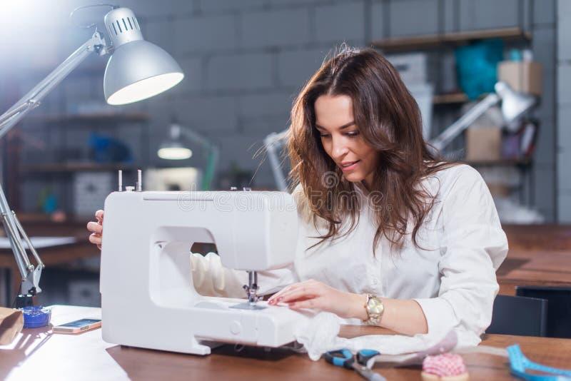Arbeitendes Nähen der attraktiven kaukasischen Näherin mit Nähmaschine an ihrem Arbeitsplatz im Studiodachbodeninnenraum stockfoto