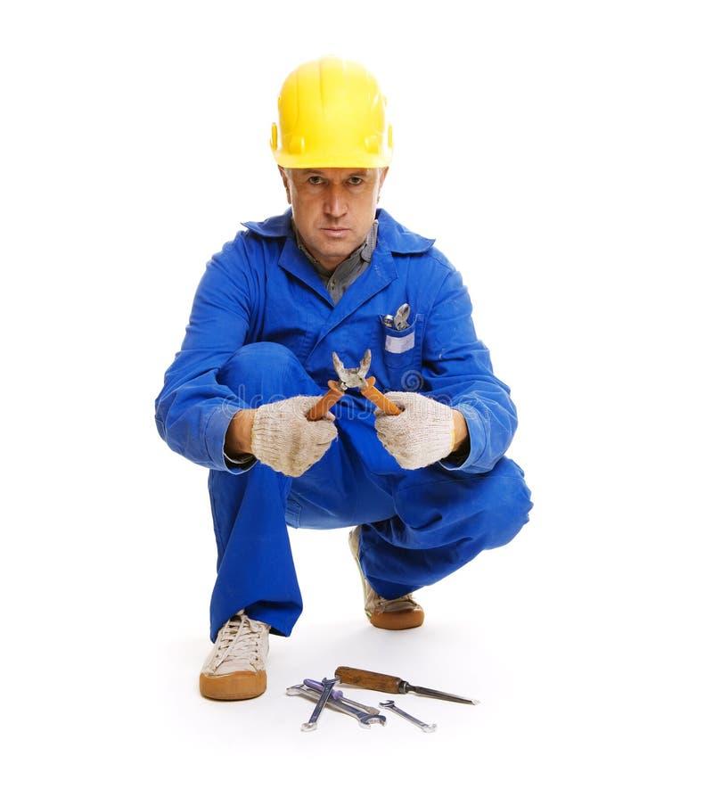 Arbeiter, der auf dem Fußboden sitzt lizenzfreie stockfotos