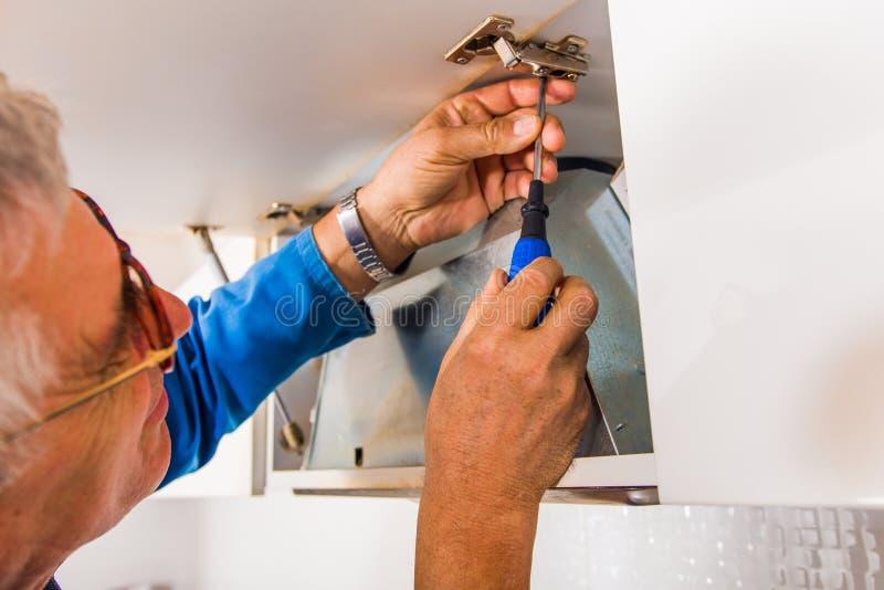 Arbeiter, der den Schrank repariert stockbild
