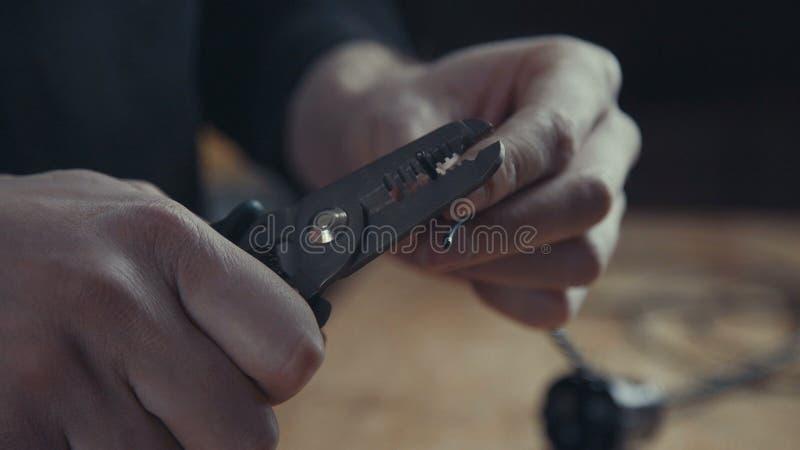 Arbeiter, der eine elektrische Leitung repariert oder unter Verwendung der Zangen verdrahtet stockbild