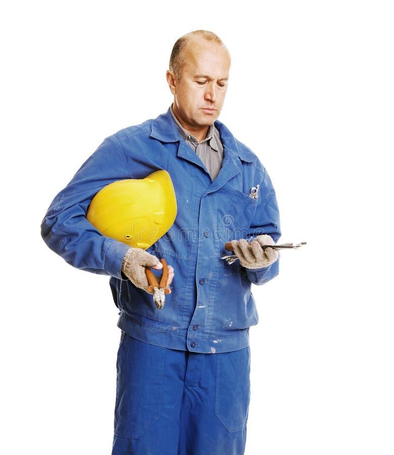 Arbeiter, der Hilfsmittel betrachtet lizenzfreies stockbild