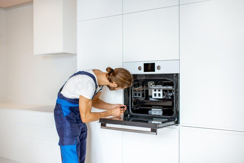 Arbeiter, der Küchenofen installiert lizenzfreies stockfoto