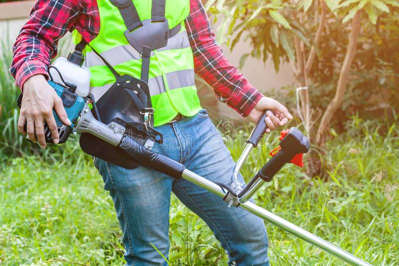 Arbeiter, der Rasenmäher-Maschinenausschnittgras hält lizenzfreie stockfotos