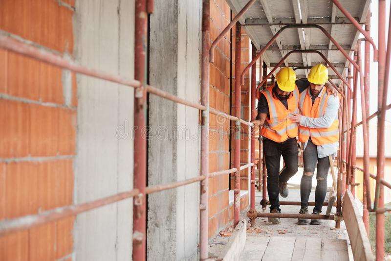 Arbeiter, der verletztem Kollegen in der Baustelle hilft stockbilder