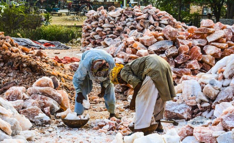 Arbeiter, die Klumpen des Steinsalzes laden stockfotografie