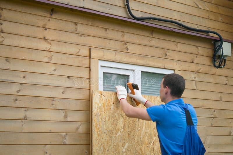 Arbeiter, im Fenster des Hauses mit einer Schutzschild aus Holz, vor Diebe, beim Umzug in eine andere Adresse stockfotos