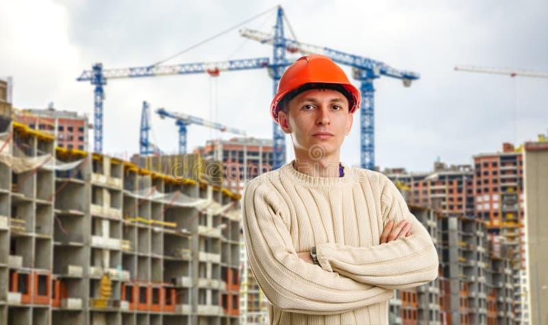 Arbeiter im roten Sturzhelm auf Hintergrund von Gebäuden stockfotografie