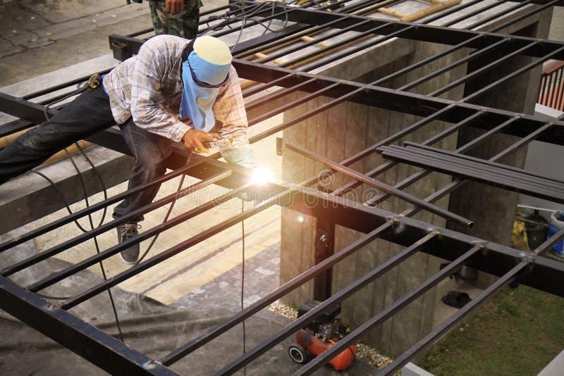 Arbeiter stellen Stahldächer malten schwarz her stockfotografie