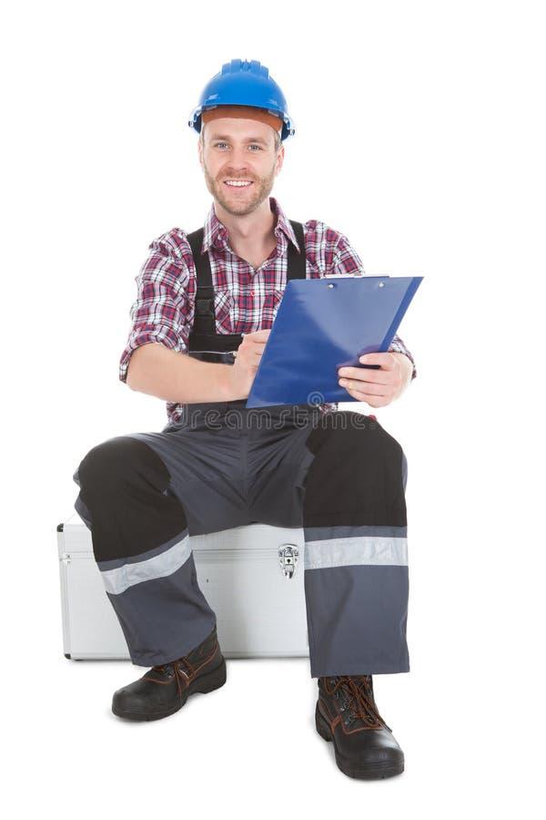 Arbeitersschreiben auf Klemmbrett über weißem Hintergrund stockbilder