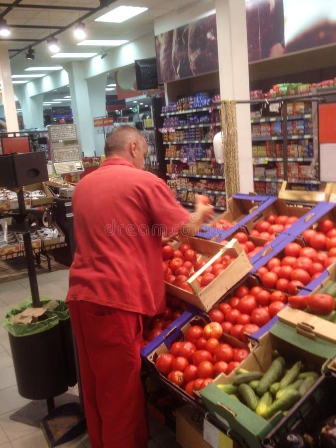 Arbeitgeber, der Frischgemüse am Supermarkt sortiert lizenzfreie stockfotos