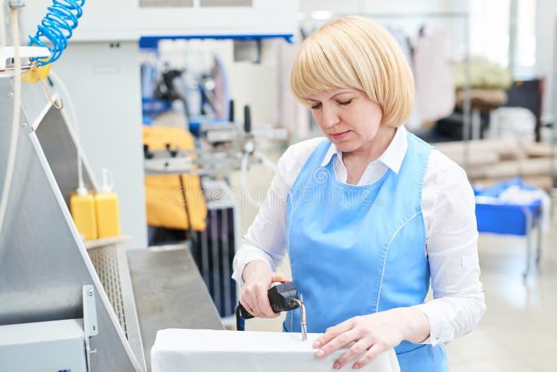 Arbeitnehmerin in der Wäschereiprozess-Fleckenentfernung lizenzfreie stockfotos