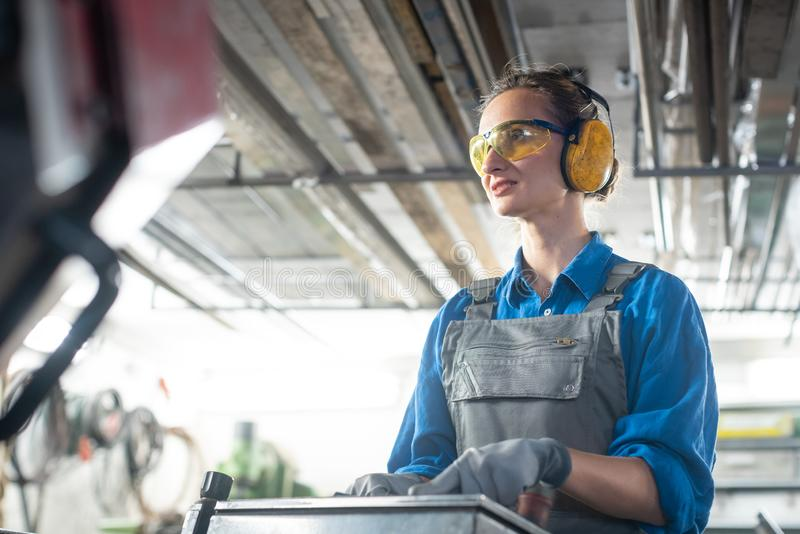 Arbeitnehmerin, die eine Werkzeugmaschine in der Metallwerkstatt oder dem facto betreibt stockbild