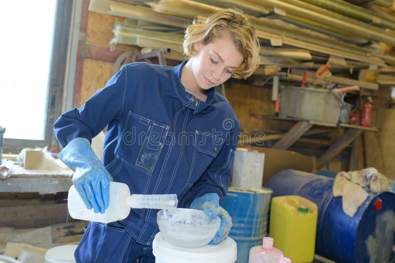 Arbeitnehmerin, die Fiberglas herstellt, um Boot in der Werkstatt zu reparieren lizenzfreies stockbild