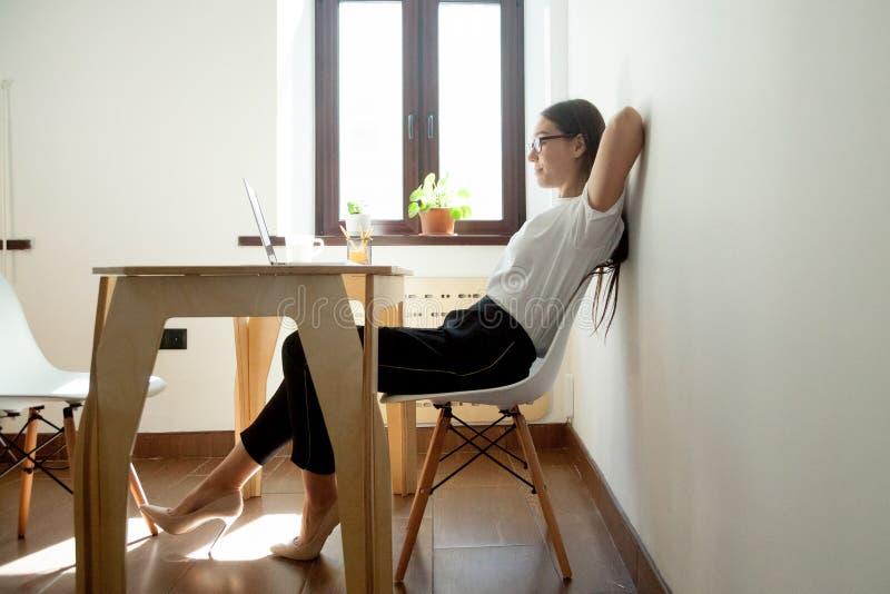 Arbeitnehmerin, die im entspannenden Stuhl sich lehnt stockfotos