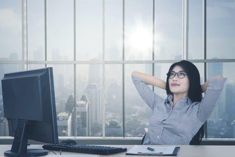 Arbeitnehmerin, die nahe dem Fenster sich entspannt lizenzfreies stockbild