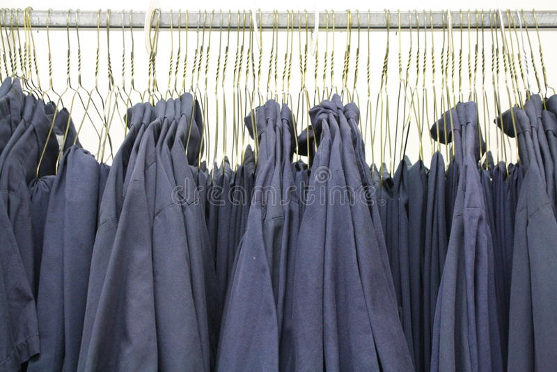 Arbeits-Hemduniformen des blauen Kragens auf Aufhängern lizenzfreie stockfotos