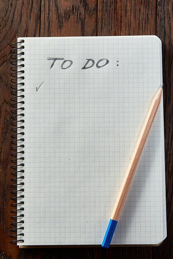 Arbeitsbuch und ein Bleistift auf einem hölzernen Hintergrund, Draufsicht stockbild