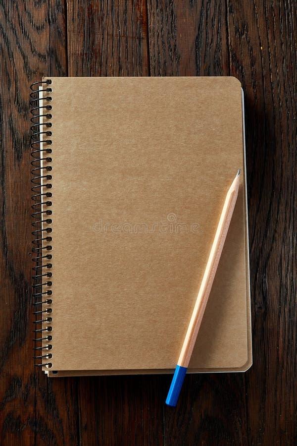 Arbeitsbuch und ein Bleistift auf einem hölzernen Hintergrund, Draufsicht lizenzfreies stockfoto