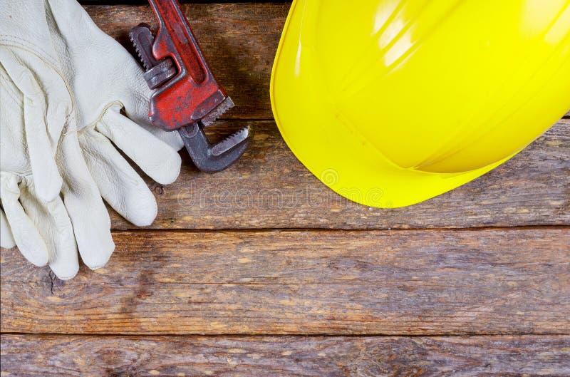 Arbeitshandschuhe, errichtender Sturzhelm und Gl?ser, Werkzeugausr?stung auf h?lzerner Tabelle stockbild