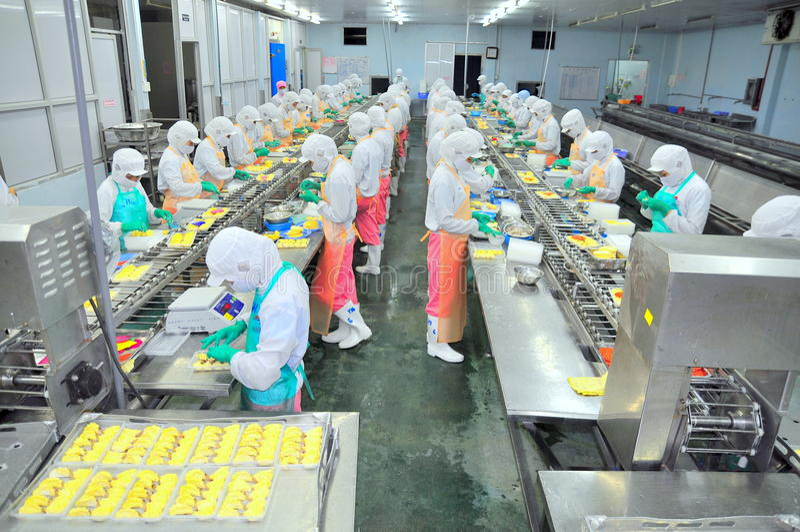 Arbeitskräfte arbeiten stark an einer Fertigungsstraße in einer Meeresfrüchtefabrik in Ho Chi Minh-Stadt, Vietnam stockbilder