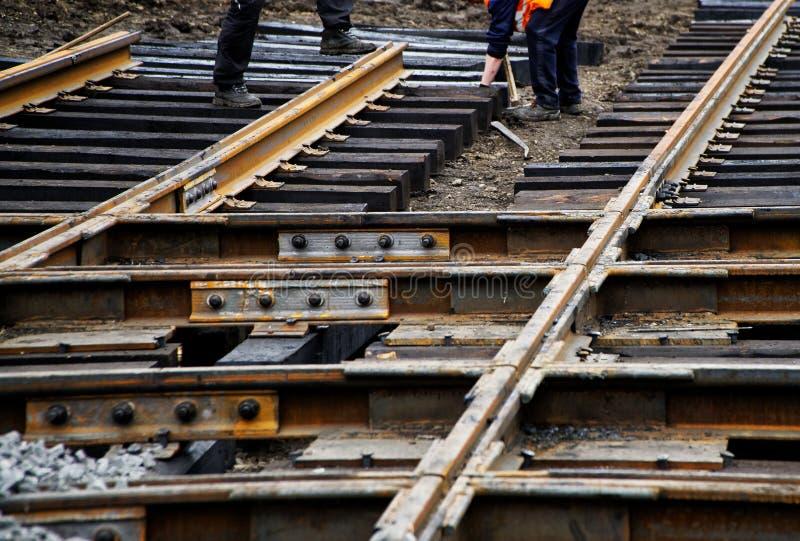 Arbeitskräfte bauen Holzschwellen und Rillenschienen während der Reparatur von Stadtstraßen zusammen stockfoto
