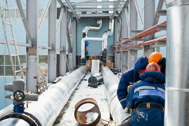 Arbeitskräfte bauen Rohrleitungen zusammen stockfotografie