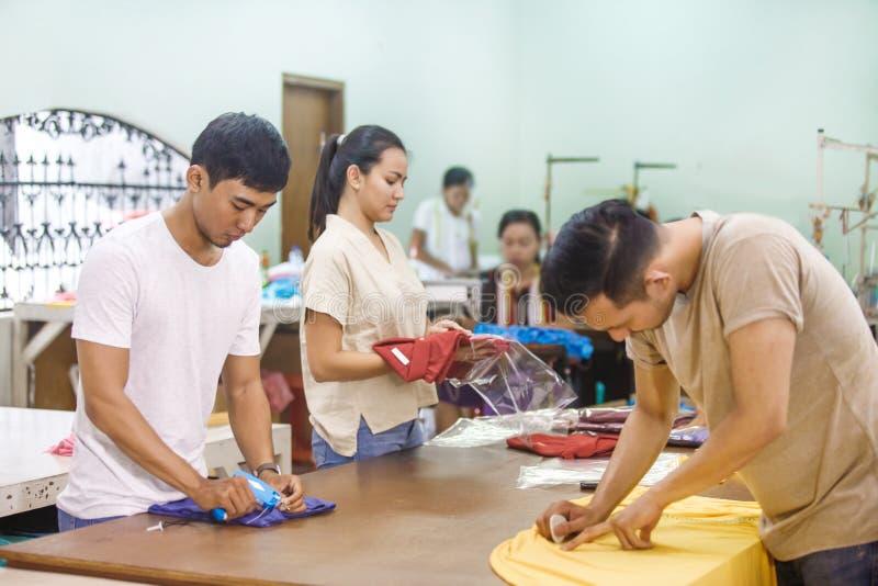 Arbeitskräfte bei der Textilfirma, die ein Gewebe, eine Kennzeichnung und einen Satz markiert lizenzfreie stockfotos