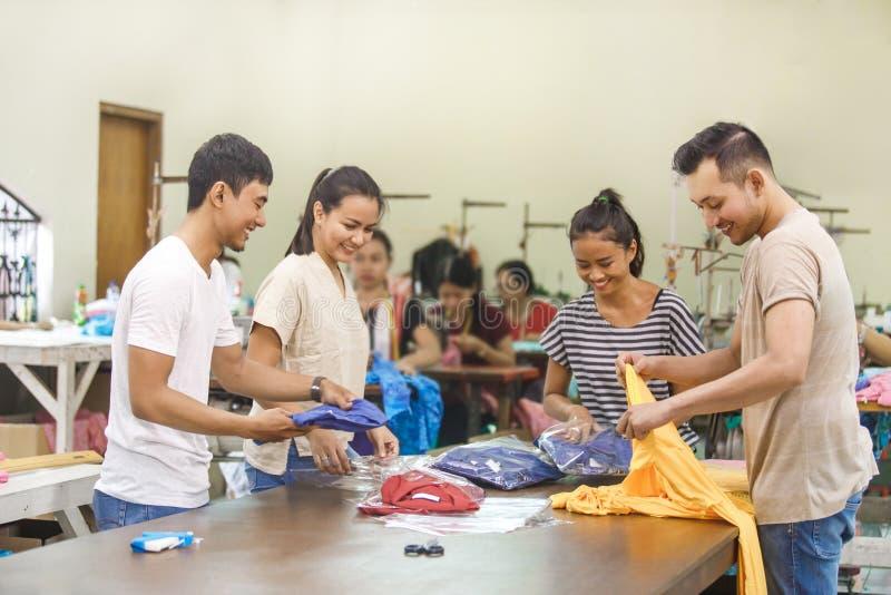 Arbeitskräfte bei der Textilfirma, die ihr Qualitätsprodukt steuert lizenzfreie stockfotografie