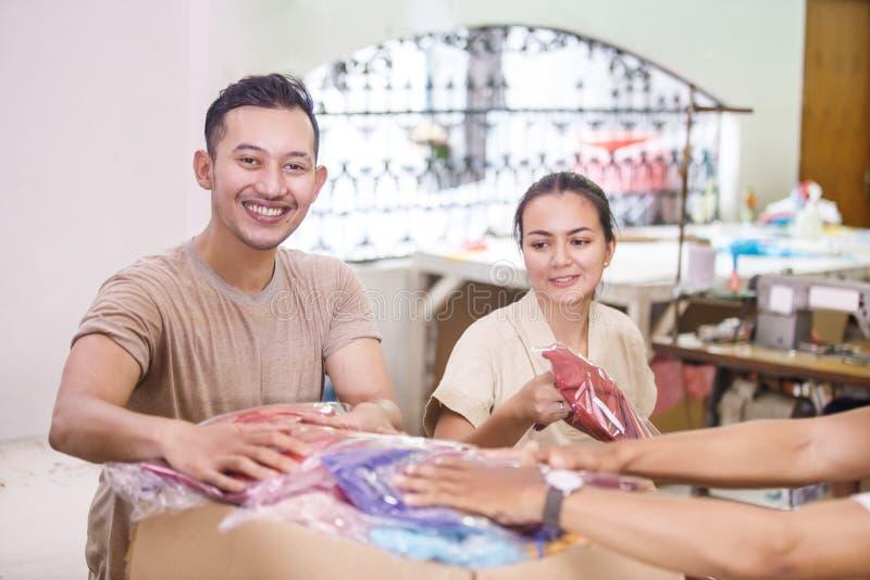 Arbeitskräfte bei der Textilfirma, die ihre Produkte in einen Kasten stapelt lizenzfreie stockfotografie
