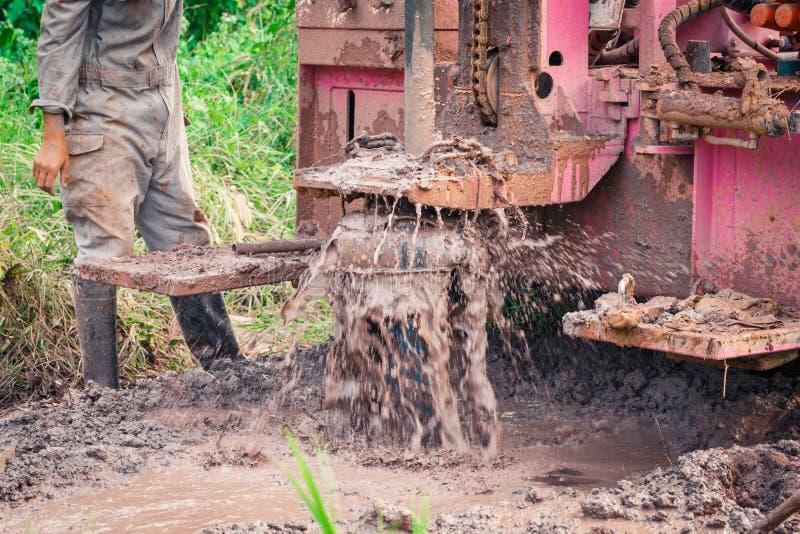 Arbeitskräfte benutzen Bohrmaschineunschärfe des Grundwassers lizenzfreies stockfoto