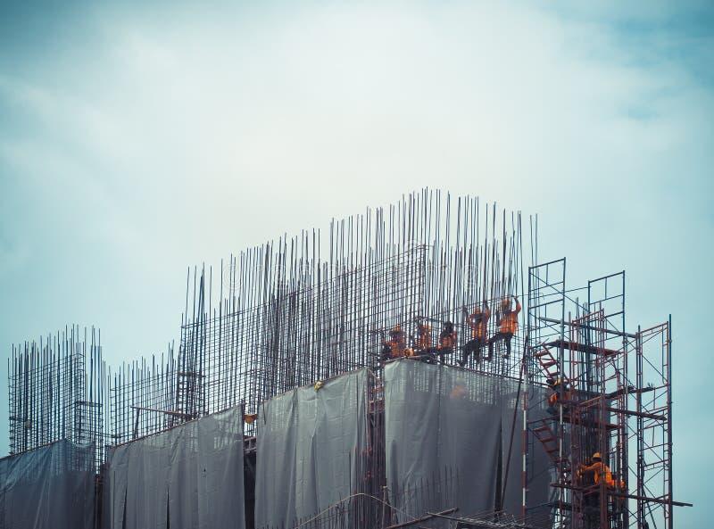 Arbeitskräfte in der Baustelle werden oben mit Stahlkonstruktionen gebunden lizenzfreie stockfotos