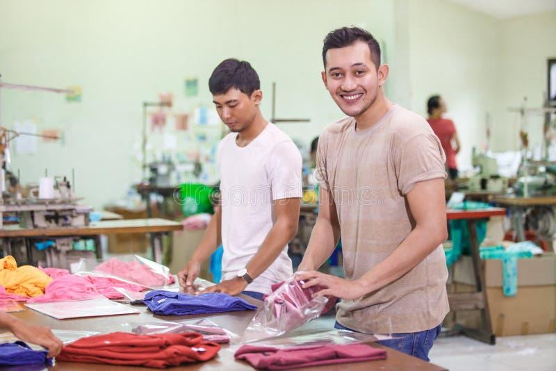 Arbeitskräfte an der Textilfabrik, die ihre Produkte während smilin verpackt lizenzfreie stockfotos