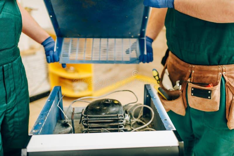 Arbeitskräfte in der Uniform entfernt Abdeckung des Kühlschranks lizenzfreie stockfotos