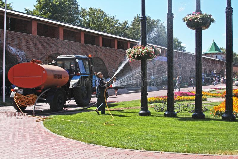 Arbeitskräfte, die Blumen mit einem Schlauch innerhalb des Novgorod der Kreml in Nizhny Novgorod wässern lizenzfreies stockbild