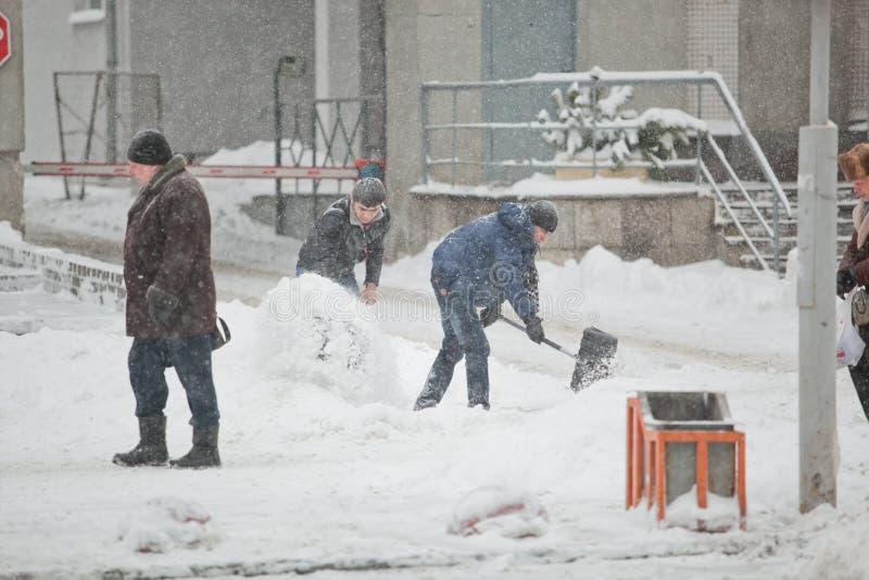 Arbeitskräfte, die den Bürgersteig im schweren Blizzard säubern lizenzfreies stockfoto