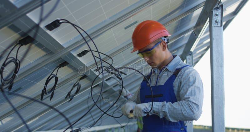Arbeitskräfte, die Drähte von Sonnenkollektoren anschließen stockfoto