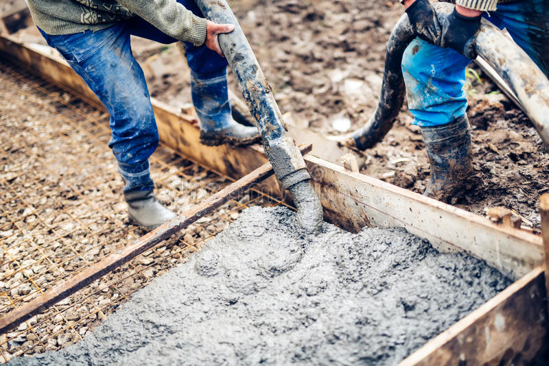 Arbeitskräfte, die enormes ZementPumpenrohr behandeln und Frischbeton auf verstärkten Stangen am Neubaustandort gießen lizenzfreie stockfotografie