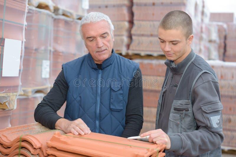Arbeitskräfte, die Fliesen des roten Backsteins kaufen lizenzfreies stockfoto