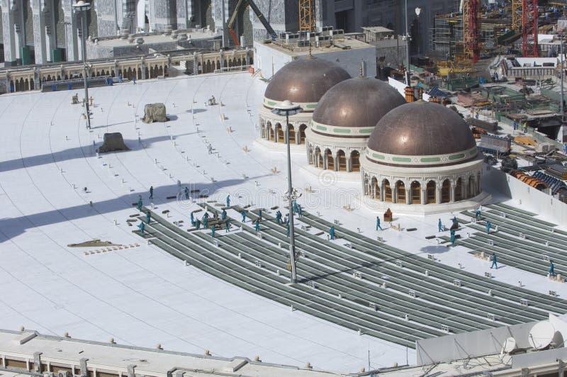 Arbeitskräfte, die Gebets-Teppiche bei Al Haram des Als-Kaaba sammeln lizenzfreie stockfotos