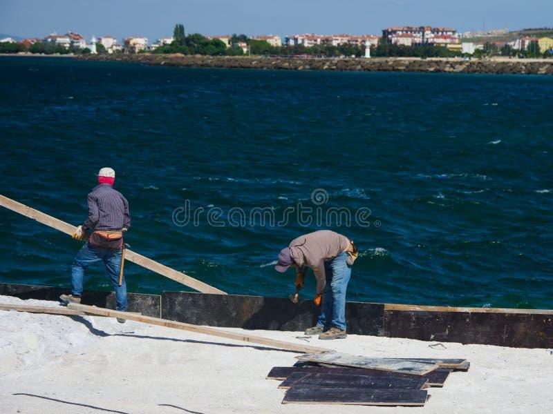 Arbeitskräfte, die am Hafen für das Verschalen der Fährüberfahrt Dardanellen-Straße in Canakkale, die Türkei arbeiten stockbild