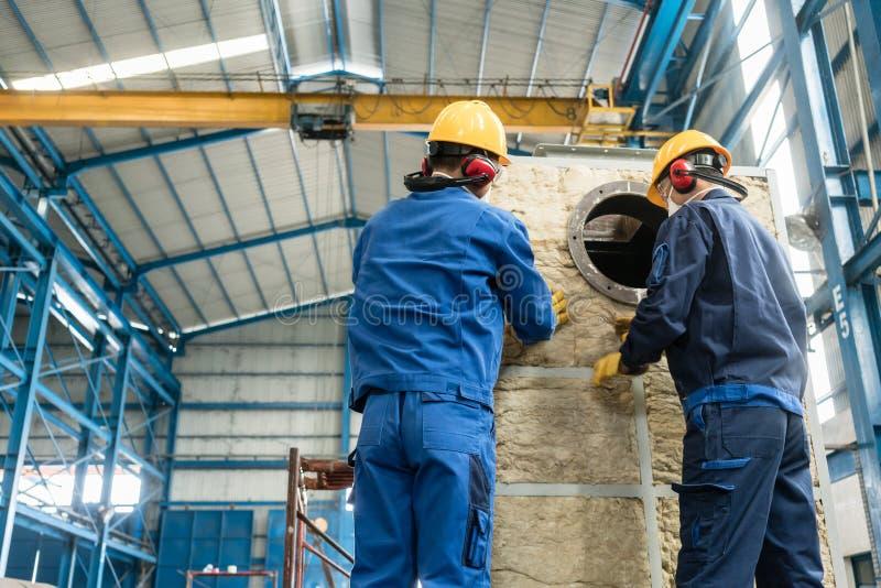 Arbeitskräfte, die Isoliermaterial auf einen Industriekessel zutreffen lizenzfreie stockfotos