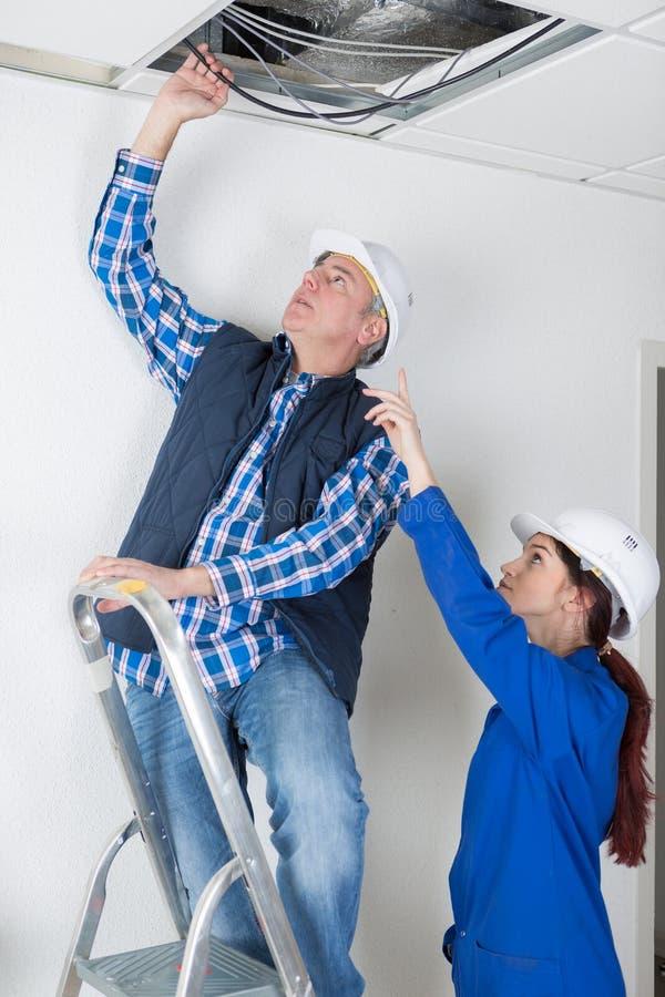 Arbeitskräfte, die Rohrleitung auf Gebäudedecke reparieren lizenzfreie stockfotos