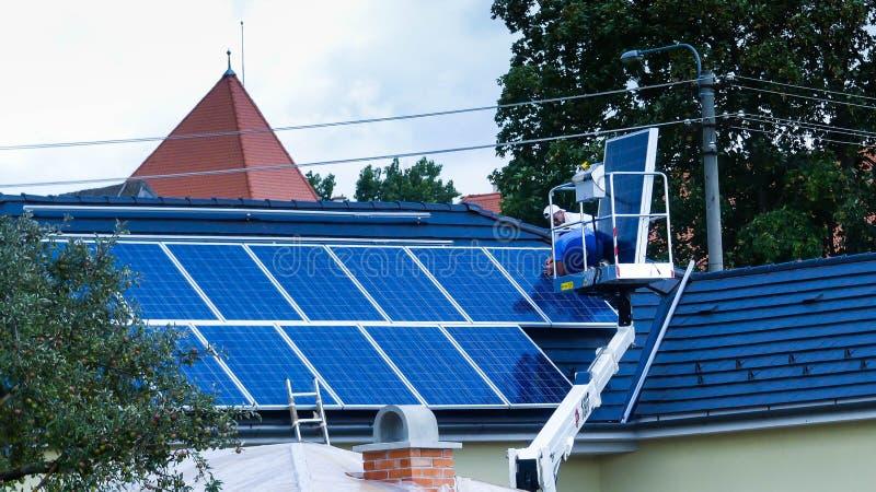 Arbeitskräfte, die Sonnenkollektoren am residentual Haus anbringen stockbild