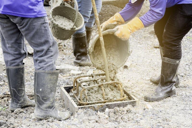 Arbeitskräfte gießen Beton aus dem Behälter heraus, um einen Stapelcasting zu machen stockfotos